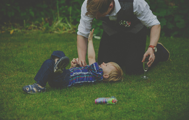 A little boy lies on his back on the grass and plays with his father