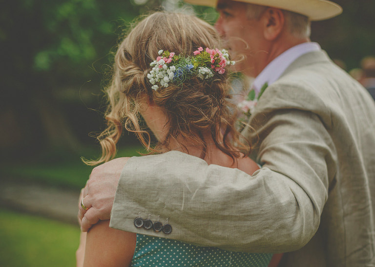 The brides father puts his arm around a bridesmaid on the front lawn at Markington Hall