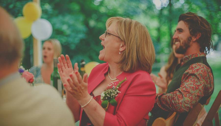 The brides mother claps her hands in the marquee