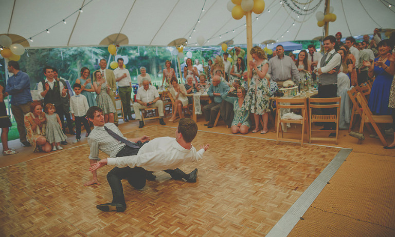 Two wedding guests dance with each other on the dancefloor in the marquee