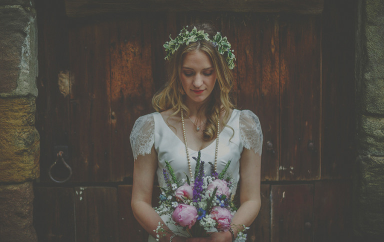 The bride stands in front of a wooden door and looks down at her bouquet