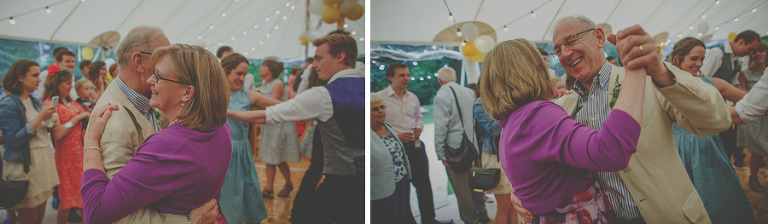 The brides mother and father dance on the dancefloor in the marquee