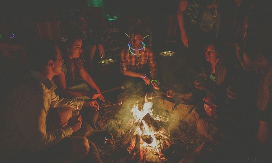 Wedding guests sit around the open campfire at Copper Beech Glade