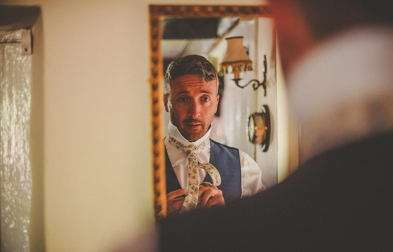 The groom gets ready and looks in the mirror as he adjusts his tie