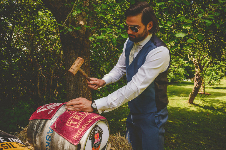 The best man hammers a cork into the beer barrel