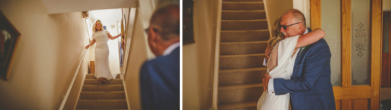 The bride walks down the stairs of her parents house and greets her father