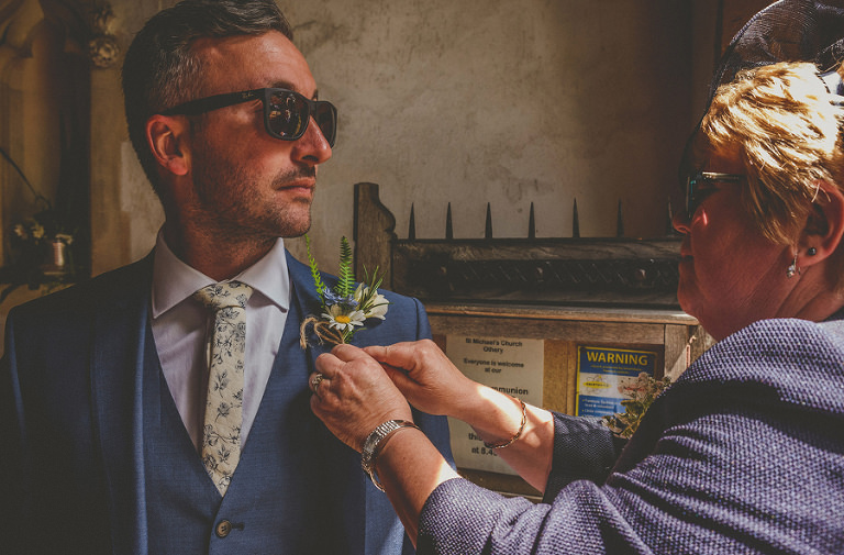 The brides mother adjusts the flower lapel on the grooms jacket
