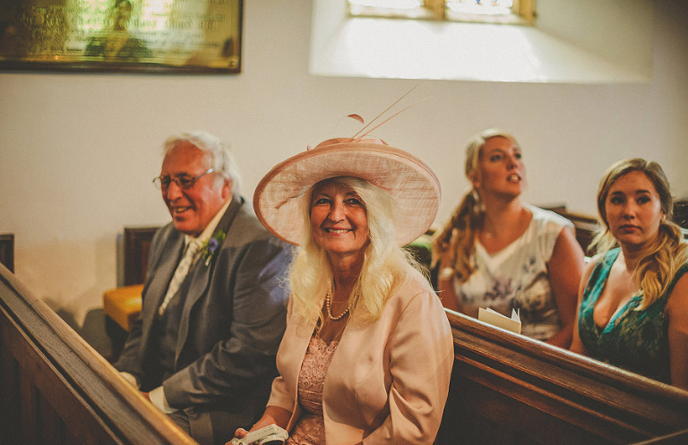 The grooms mother and father sit in church waiting for the bride to arrive