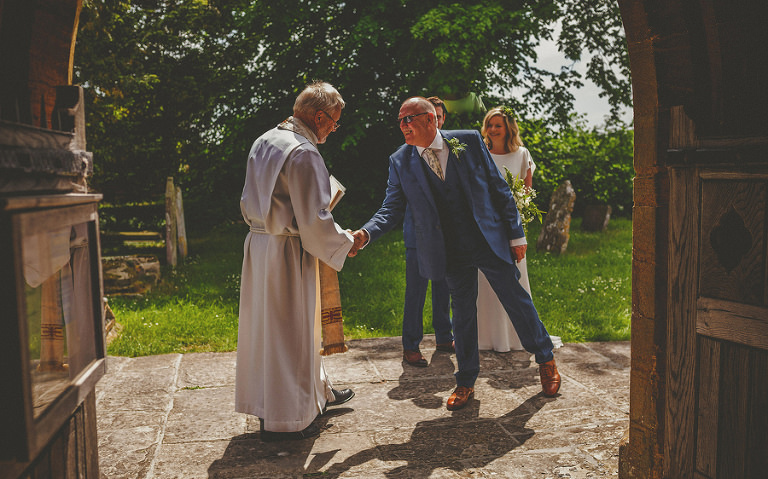 The bride arrives at the church and greets the vicar