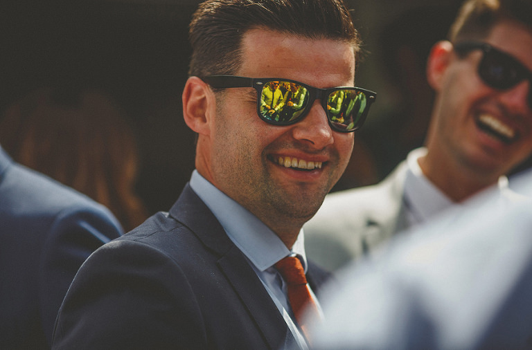 A man with sunglasses smiles at the bride and groom