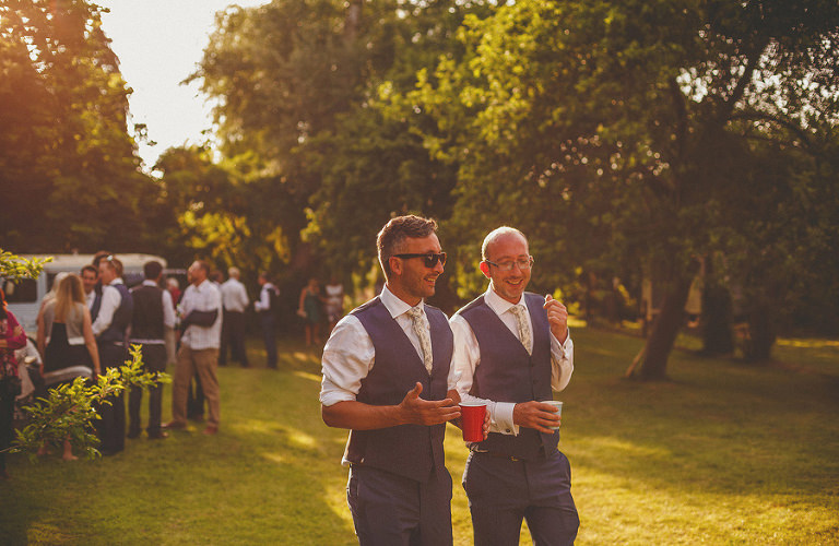 The groom and his brother share a joke as the sun goes down