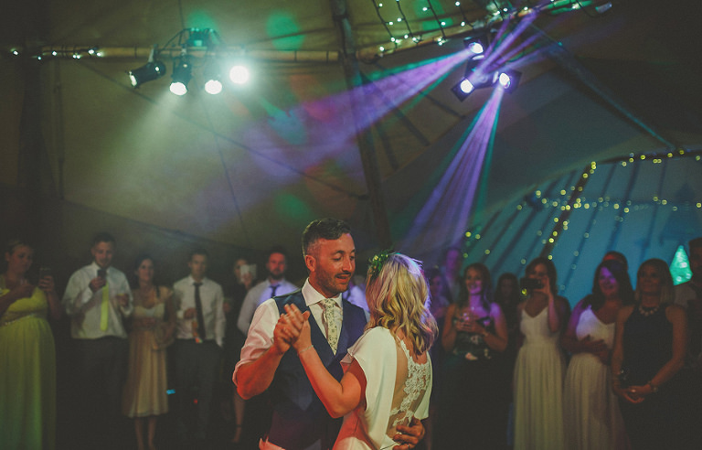 The groom smiles at the bride on the dancefloor during the first dance