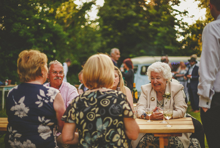 The wedding party enjoy drinks in the garden