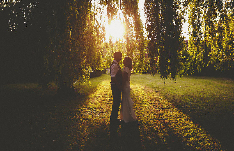 The bride and groom under a weeping willow tree