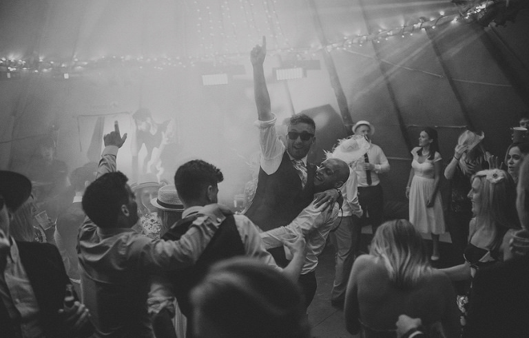 The groom lifts his arm in the air as his friends dance around him