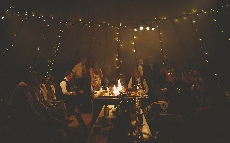 Wedding guests gather around the fire pit in the tipi