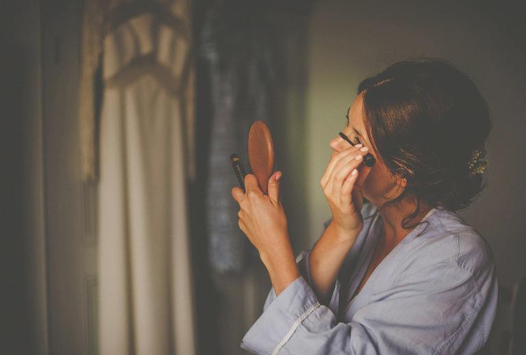 A bridesmaid puts on mascara