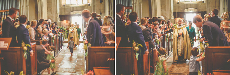 The vicar walks the bridal party down the aisle of the church