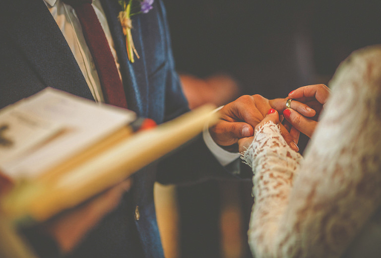 The bride puts a ring on the finger of the groom