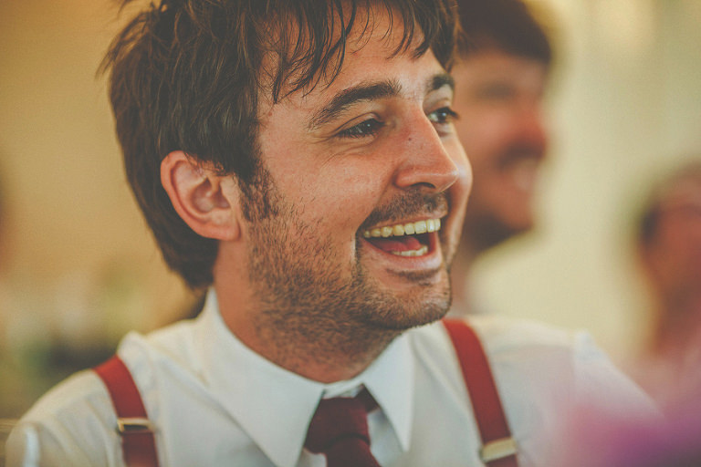 The groom laughs at the brides joke