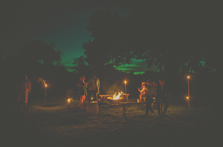 A crowd gather around the outdoor fire pit