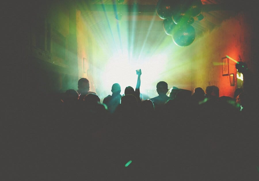 Lights across the dancefloor make silhouettes of the crowd