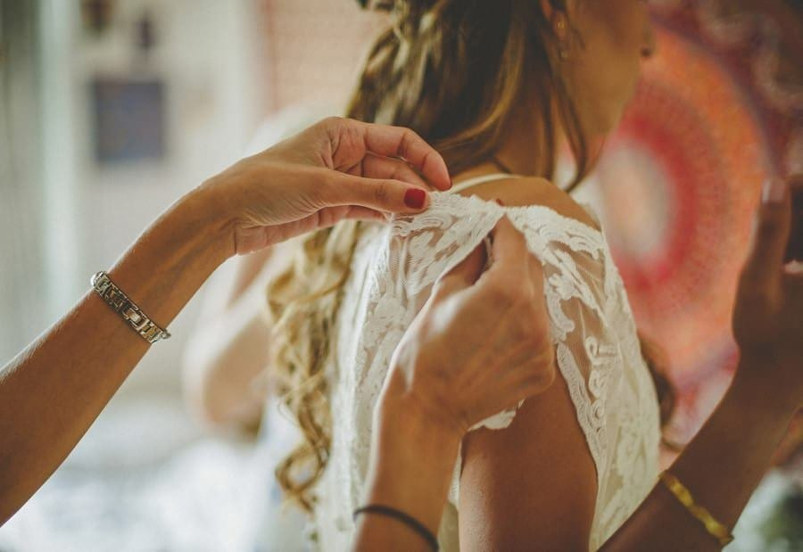 The back of the brides dress is straightened by the bridesmaid