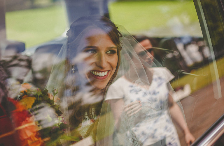 The bride looks out of the car window and smiles at one of the bridesmaids