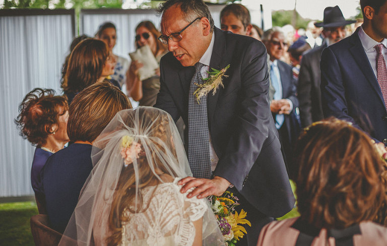 The brides father places his hands on his daughters shoulders