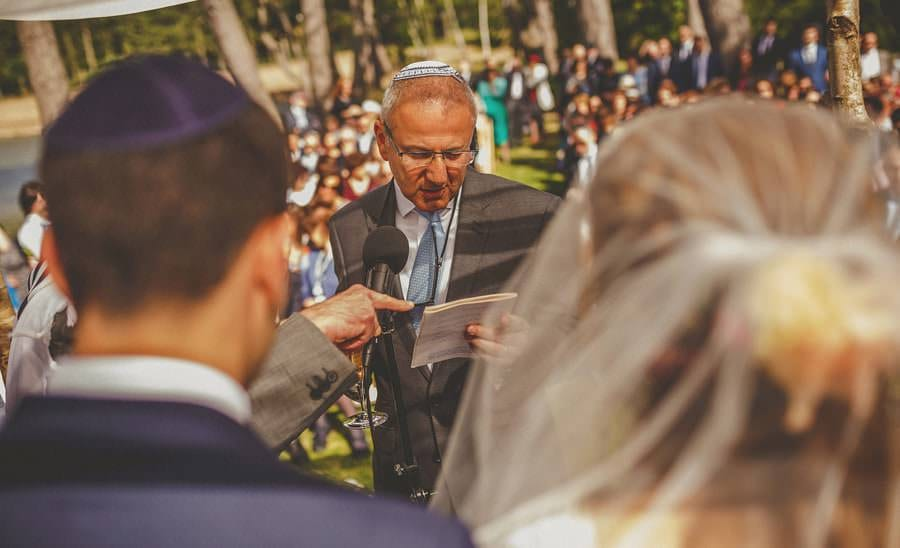 A man holds a microphone in front of the bride and groom