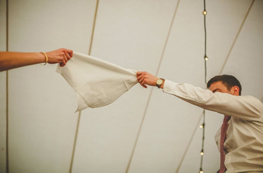 The bride and groom hold a handkerchief in the air