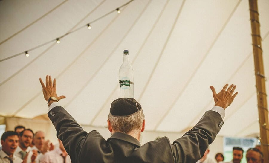 A jewish man balances a bottle of water on his head in the marquee