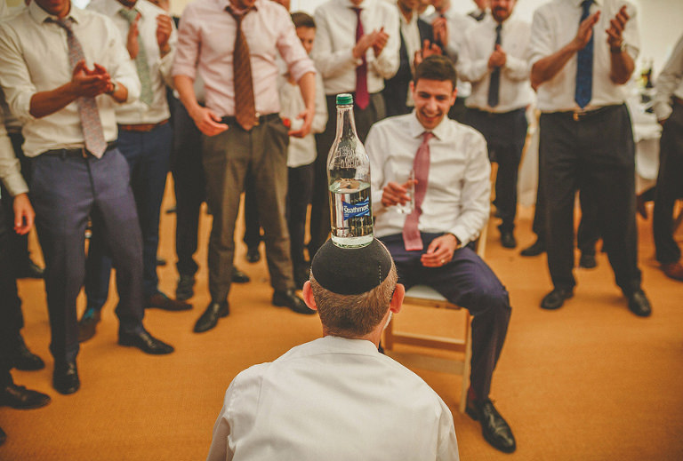 A jewish man faces the groom with a bottle of water on his head
