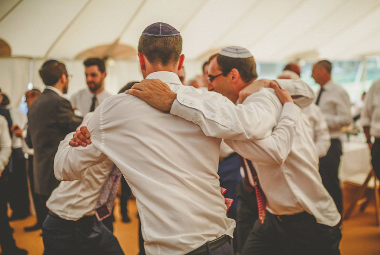 Wedding guests hold each other and dance in the marquee