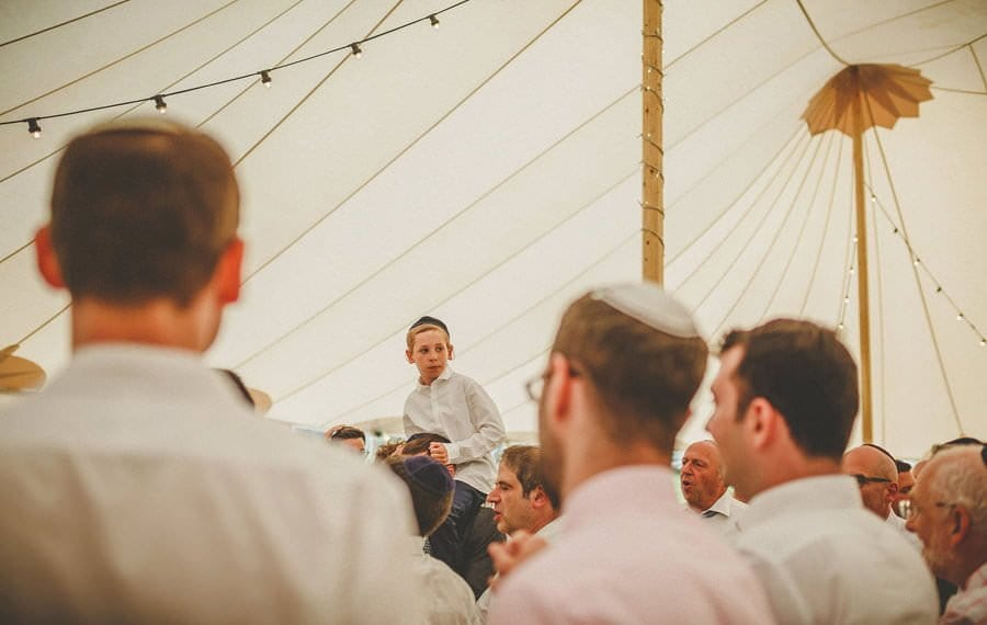 A jewish boy sits on the shoulders of his father on the dancefloor of the marquee
