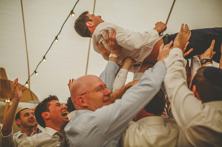 The groom is lifted in the air by men on the dancefloor of the marquee