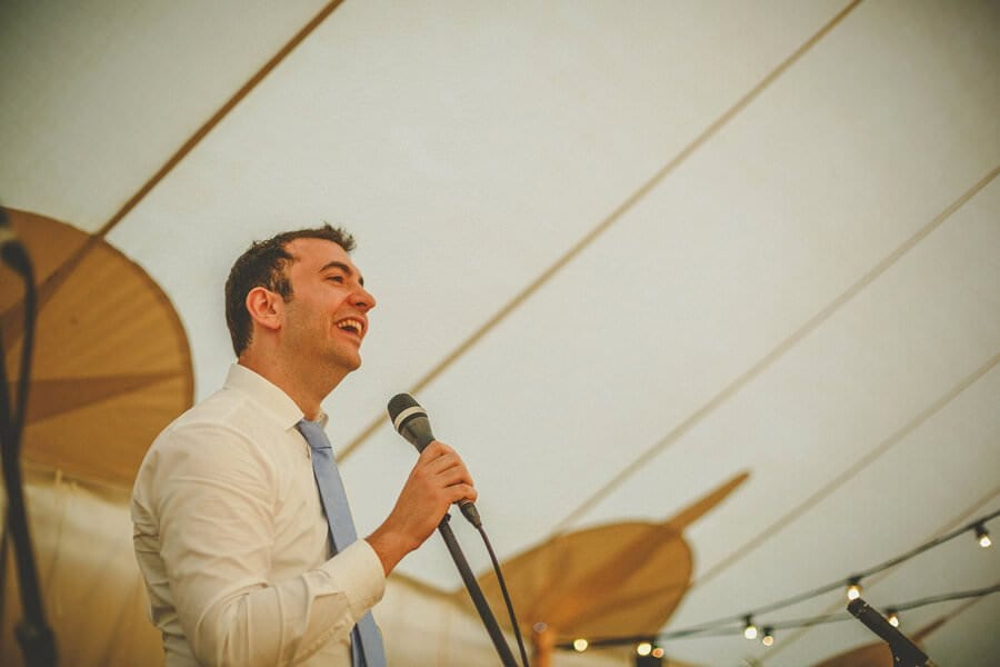 A man speaks to the wedding guests in the marquee