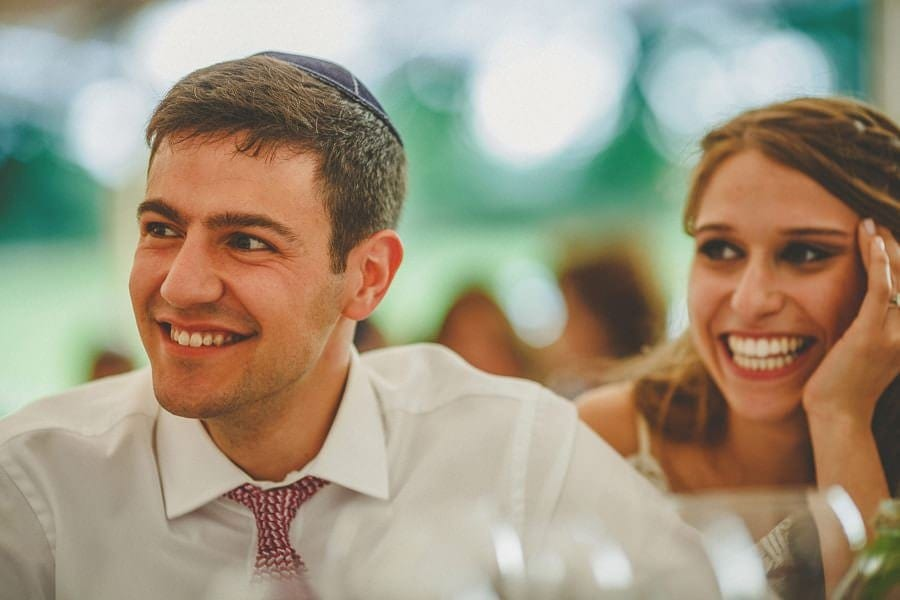The bride and groom sit at the table and smile as they listen to a speech