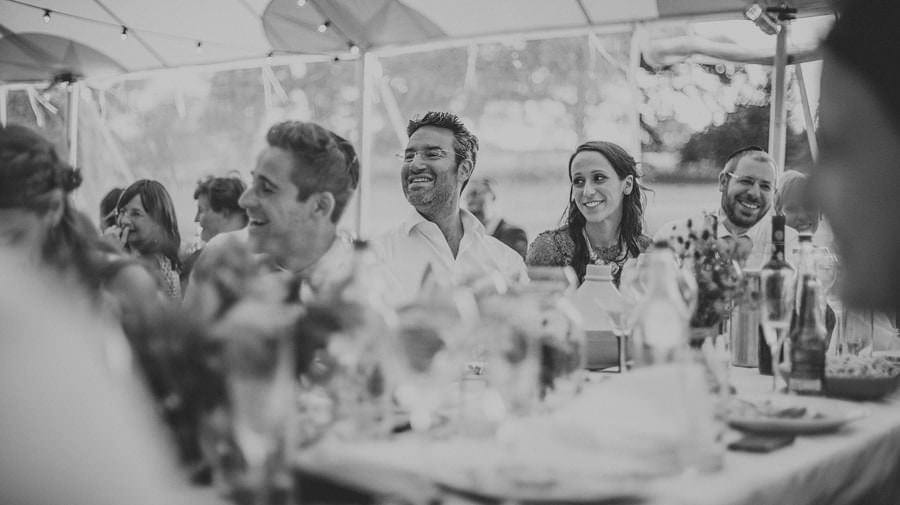 Wedding guests sat at the table listening to a wedding speech