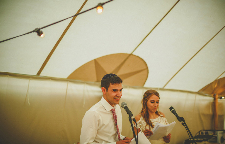The groom stands in the marquee with his bride and delivers his speech to the wedding guests