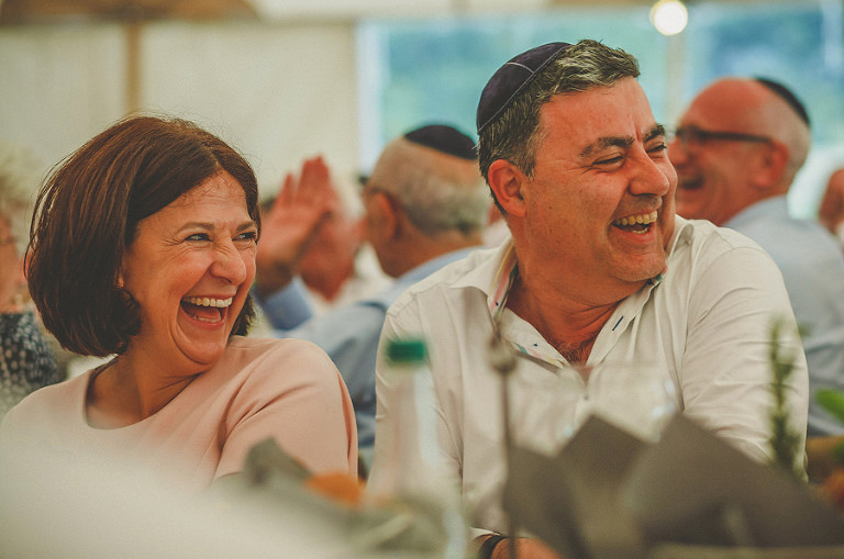 The grooms mother and father laugh at their sons speech in the marquee