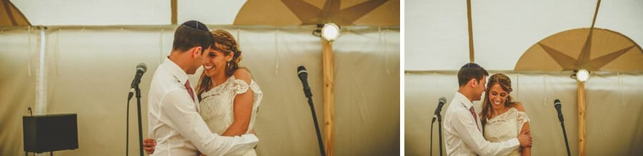 The bride and groom embrace each other in the marquee
