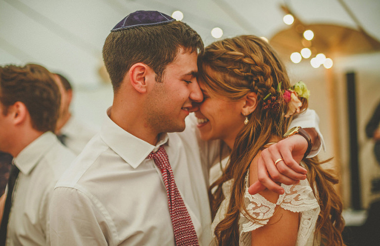 The groom holds his wife and puts his face next to hers in the marquee