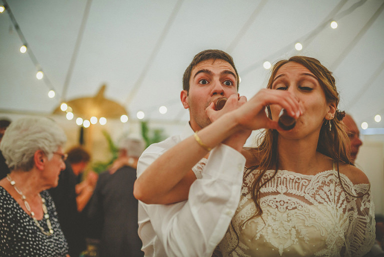 The bride and groom drink a shot of whisky together on the dancefloor in the marquee at Brook farm