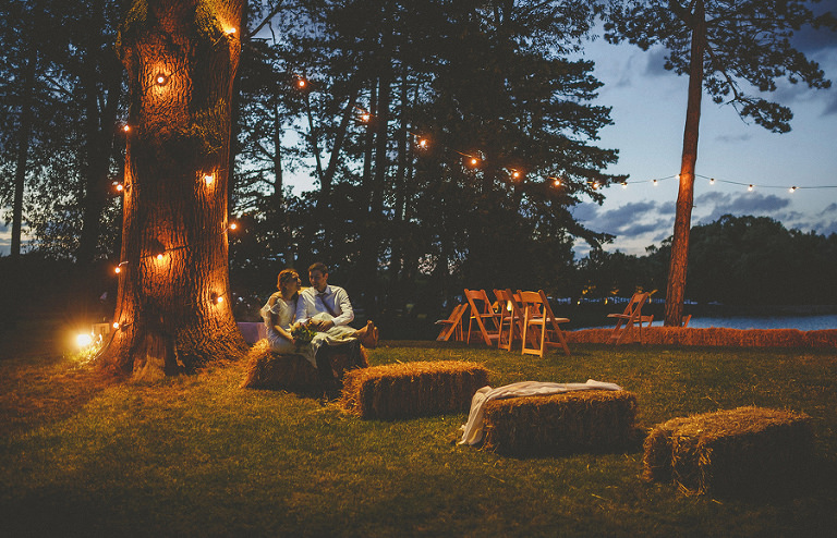 The bride and groom sit on hay bails and talk to each other as the sun goes down at Brook farm