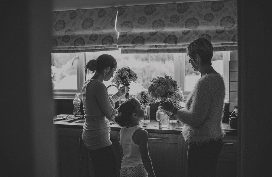 The family arrange the flowers in the kitchen
