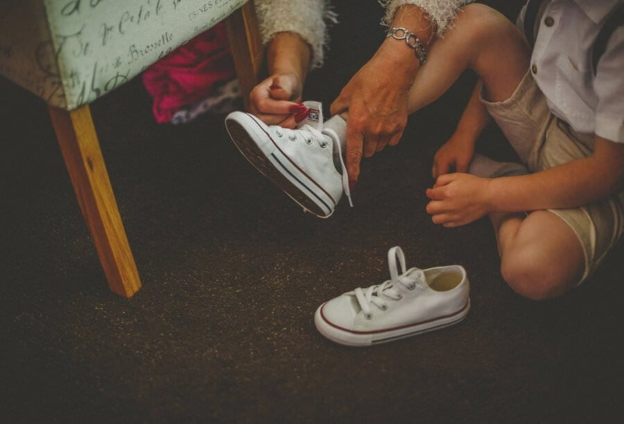 A child puts on his wedding shoes with help from his grandmother