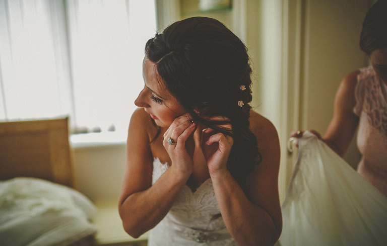 The bride puts on her earrings