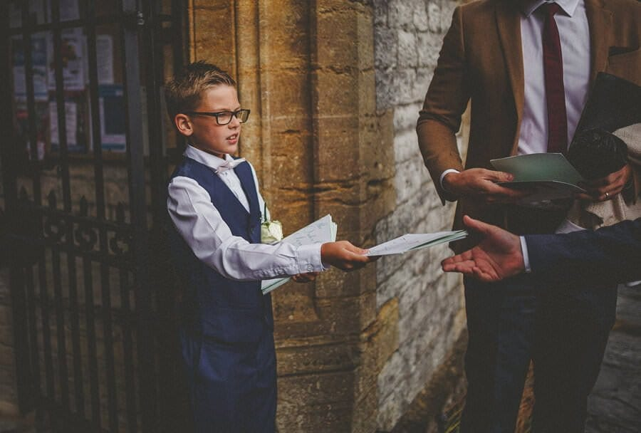 The grooms son gives out the ceremony details to the arriving guests