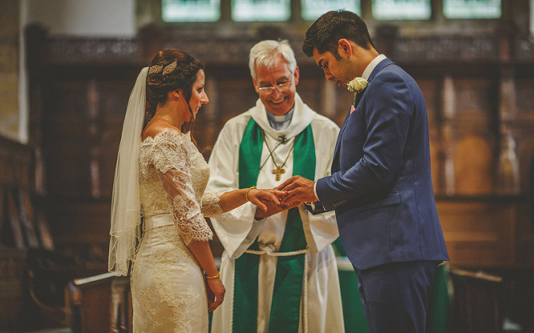 The groom puts a ring on the finger of his bride in the church during the ceremony